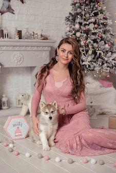 Linda garota sentada perto da árvore de natal com o cachorrinho