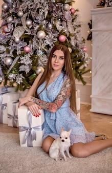 Linda garota sentada perto da árvore de natal