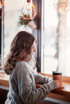 Linda garota sentada perto da janela em um café com um copo de papel de café