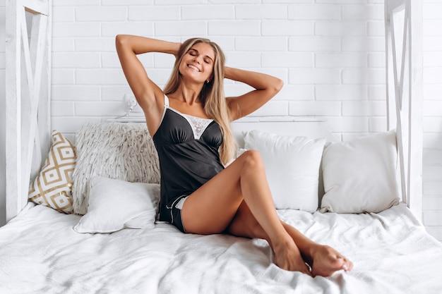 Linda garota sentada relaxa na cama de lingerie preta, fechando os olhos