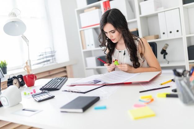 Linda garota, sentado em uma mesa de escritório, segurando uma caneta na mão e arrancando um adesivo brilhante.