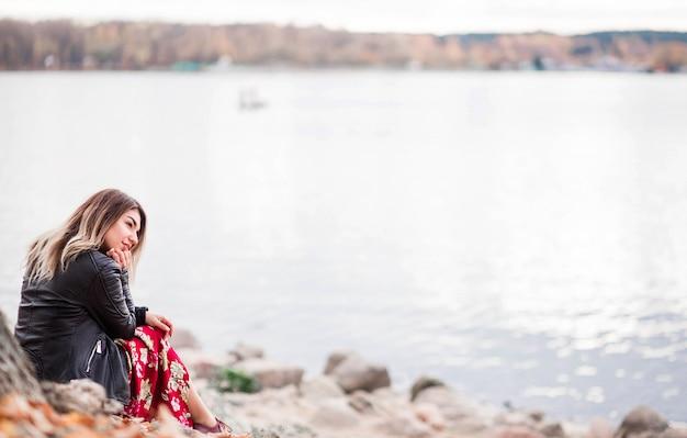 Linda garota sente-se na margem do lago e admira a vista da natureza