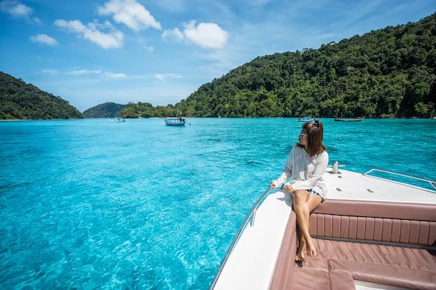 Linda garota sente-se no barco de cabeça velocidade e vendo o belo mar na ilha de surin, tailândia