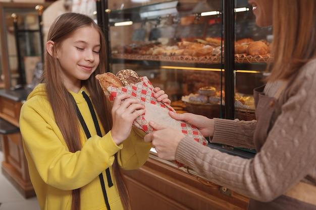 Linda garota sentindo o cheiro de pão fresco aromático que o padeiro profissional está segurando