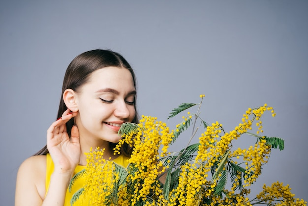 Linda garota sentindo o cheiro de uma fragrante mimosa amarela, sorrindo, curtindo a primavera
