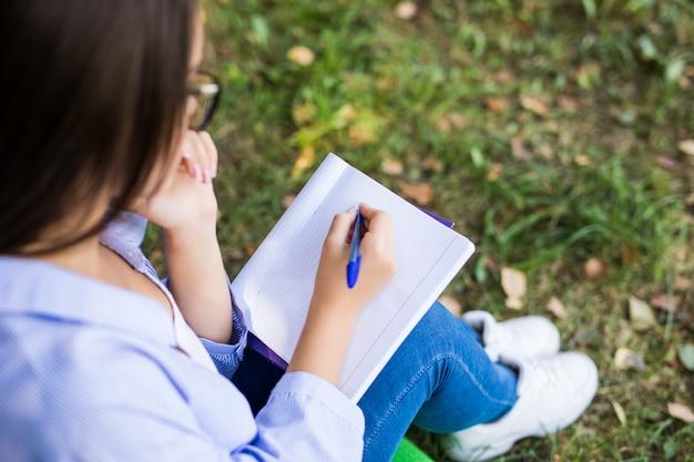Linda garota séria de cabelos escuros, com jaqueta jeans e óculos, faz sua lição de casa no parque verde de verão.