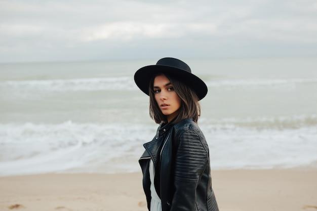 Linda garota séria no elegante casaco preto e chapéu, olhando atentamente para a câmera em pé na praia à beira-mar.
