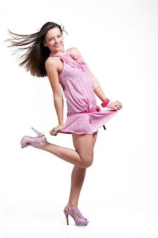 Linda garota sexy com cabelo comprido em um vestido rosa claro