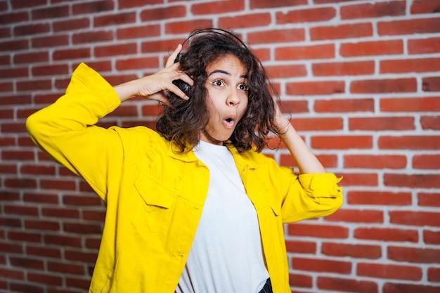 Linda garota sexy com uma jaqueta amarela ouvindo música em fones de ouvido em um fundo de parede de tijolos