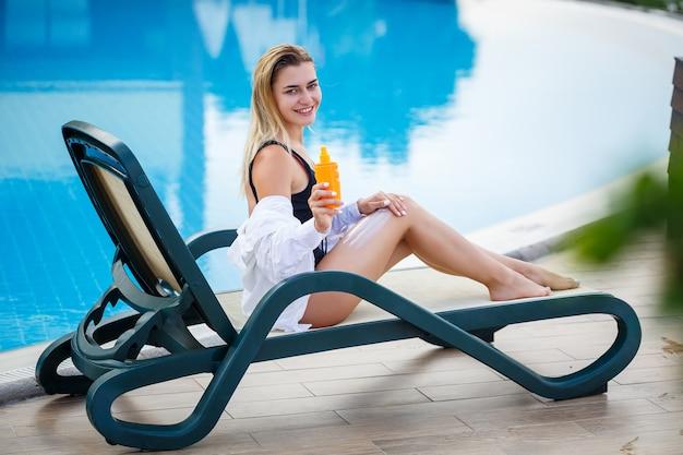 Linda garota sexy em um maiô preto senta-se à beira da piscina e passa protetor solar no corpo