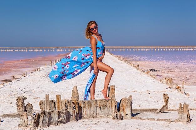 Linda garota sexy em um vestido azul posando em um lago salgado rosa. photoshoot de uma garota bronzeada