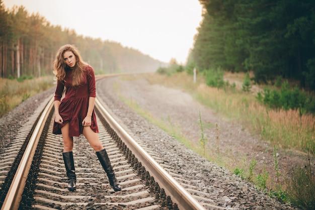 Linda garota sonhadora com cabelo natural encaracolado apreciar a natureza na floresta na estrada de ferro