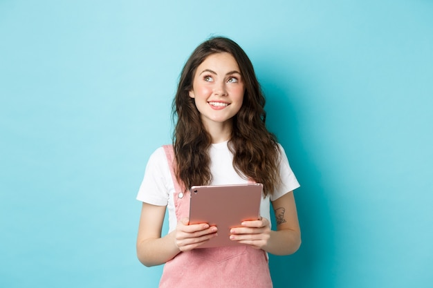 Linda garota sonhadora sorrindo, segurando o tablet nas mãos e olhando para o logotipo do canto superior esquerdo com uma cara pensativa, em pé sobre um fundo azul.