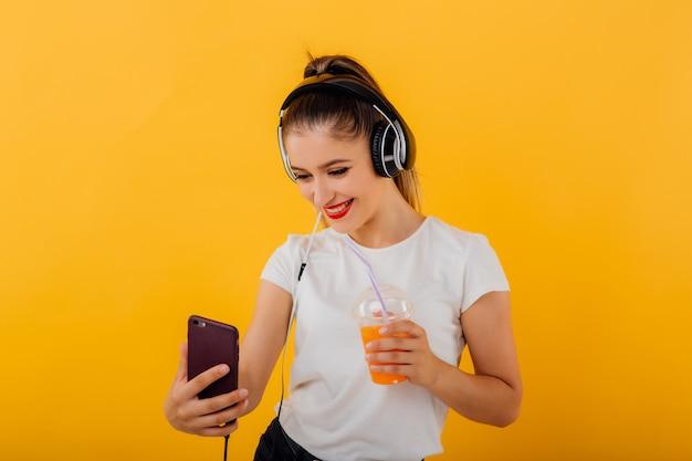 Linda garota sorri e faz o selfie, na mão do smartphone tem fones de ouvido. copo de plástico, vestido com uma camisa branca