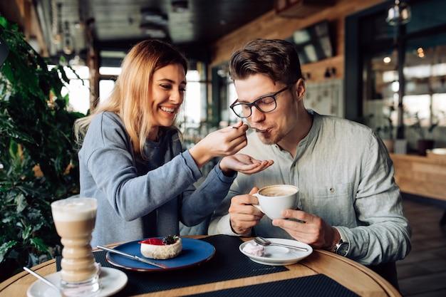 Linda garota sorridente alimenta seu namorado bonito, comendo bolo saboroso e beber café