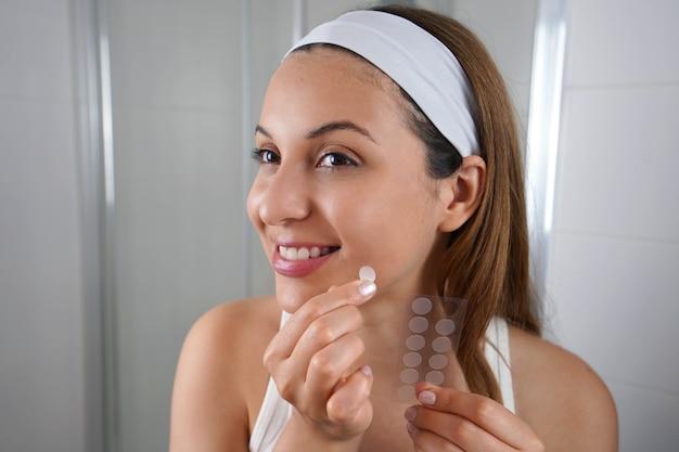 Linda garota sorridente aplicando adesivo de tratamento de acne em uma espinha no banheiro