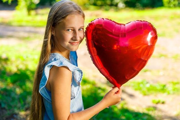 Linda garota sorridente com balão de coração