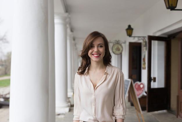 Linda garota sorridente com batom vermelho sedutor em pé na varanda do café. colunas e lanternas em segundo plano