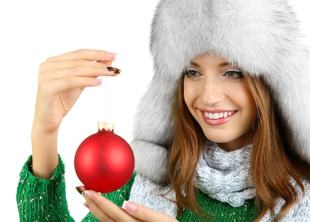 Linda garota sorridente com bola de natal isolada no branco