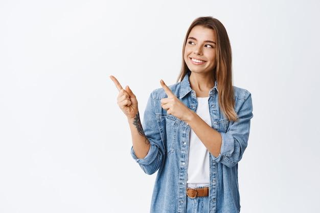 Linda garota sorridente com cabelo curto loiro, apontando e olhando para a esquerda com um sorriso satisfeito, fazendo sua escolha nas compras, encostada em uma parede branca