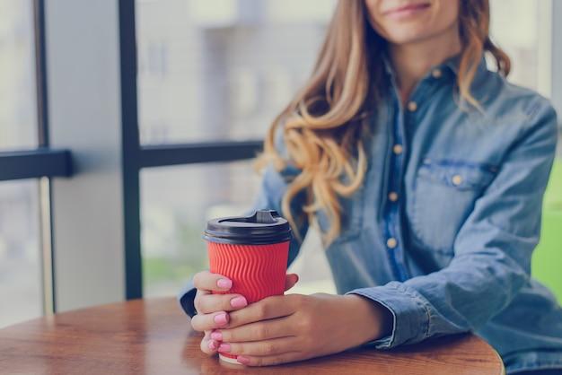 Linda garota sorridente com cabelo encaracolado, vestida com uma camisa jeans, está descansando e bebendo café matinal para viagem