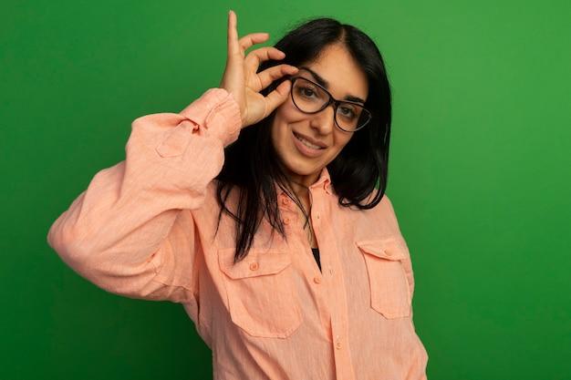 Linda garota sorridente com camiseta rosa, usando e segurando óculos isolados na parede verde