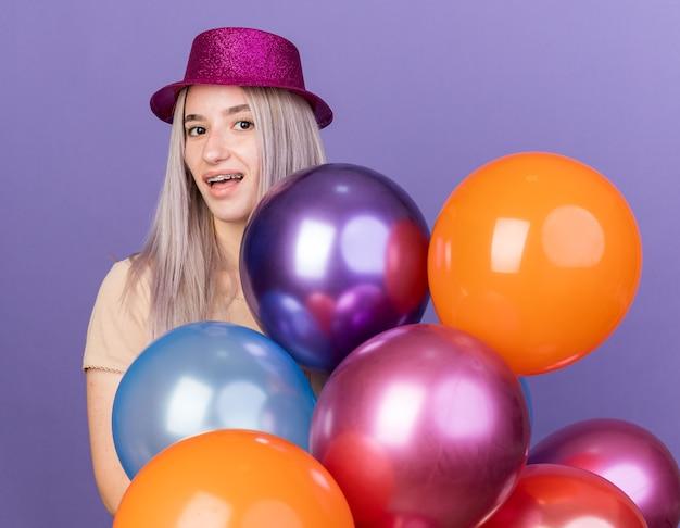 Linda garota sorridente com chapéu de festa atrás de balões
