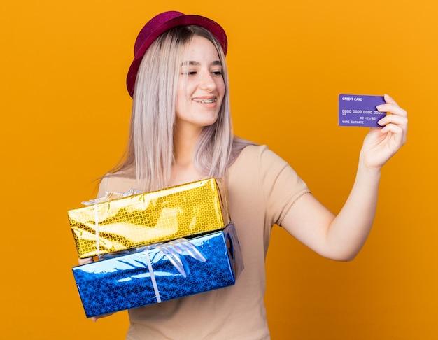 Linda garota sorridente com chapéu de festa com suspensórios segurando caixas de presente e olhando para o cartão de crédito na mão, isolado na parede laranja
