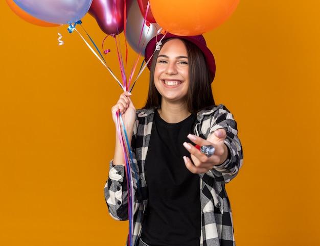Linda garota sorridente com chapéu de festa segurando balões e estendendo a mão para a câmera