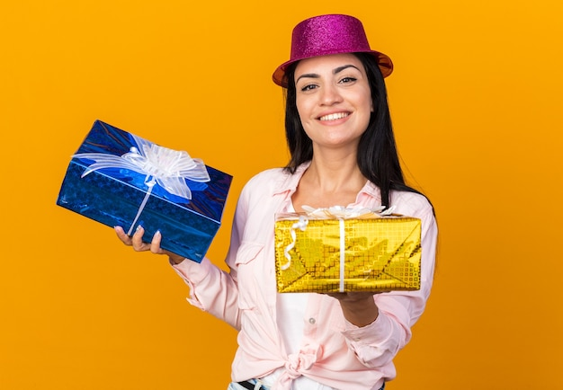 Linda garota sorridente com chapéu de festa segurando caixas de presente isoladas em uma parede laranja