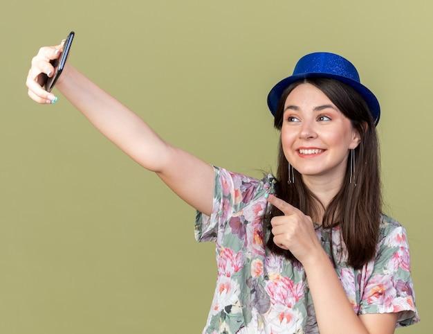 Linda garota sorridente com chapéu de festa tira uma selfie com pontos no telefone