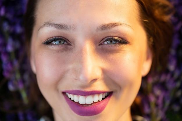 Linda garota sorridente com expressivos lábios lilás em um cenário de flores roxas