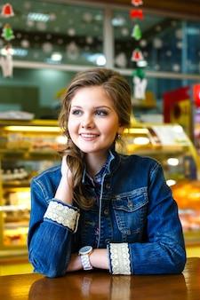 Linda garota sorridente com longos cabelos loiros sentado no café