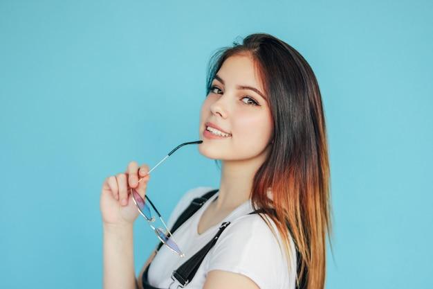 Linda garota sorridente com óculos de sol de forma de coração com cabelos longos escuros, vestindo camiseta branca isolada em azul
