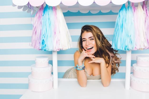 Linda garota sorridente com olhos grandes e gentis, vendendo bolos saborosos em pé atrás do balcão rosa. retrato do close-up de uma jovem atraente alegre posando com doces na parede listrada azul.