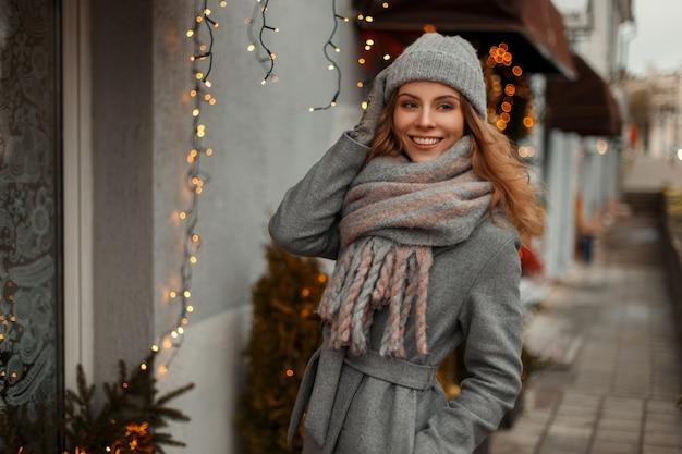 Linda garota sorridente com roupas de malha da moda com um chapéu cinza de malha e um lenço elegante caminhando ao ar livre perto das luzes amarelas