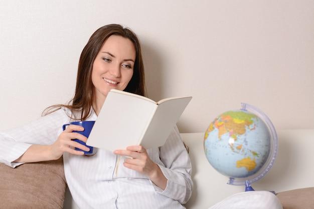 Linda garota sorridente com um copo azul e o diário, sentado no sofá na sala e lê