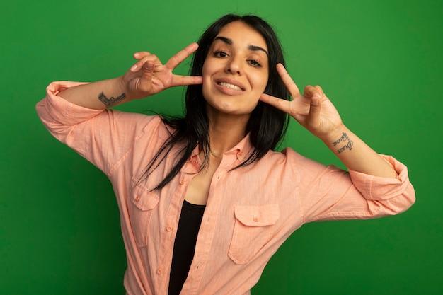 Linda garota sorridente com uma camiseta rosa mostrando um gesto de paz isolado na parede verde