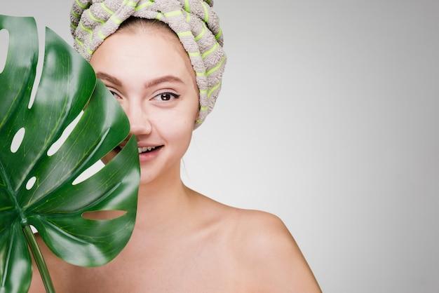 Linda garota sorridente com uma toalha na cabeça, segurando uma folha verde, day spa