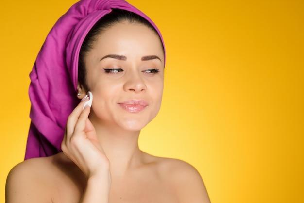 Linda garota sorridente com uma toalha rosa na cabeça limpa a pele com uma bola de algodão