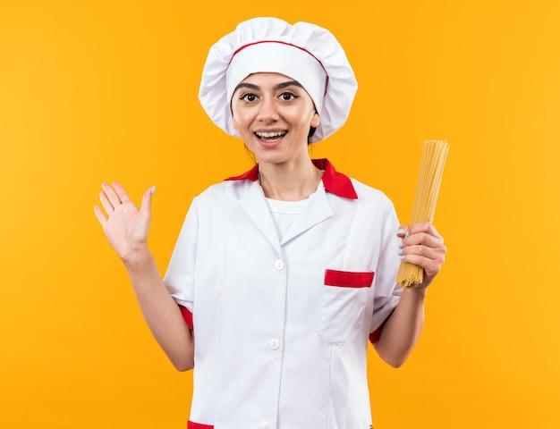 Linda garota sorridente com uniforme de chef segurando pontas de espaguete com a mão ao lado isolada na parede laranja com espaço de cópia