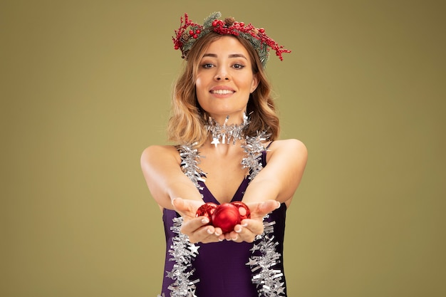 Linda garota sorridente com vestido roxo e grinalda com guirlanda no pescoço segurando bolas de árvore de natal para a câmera isolada em fundo verde oliva