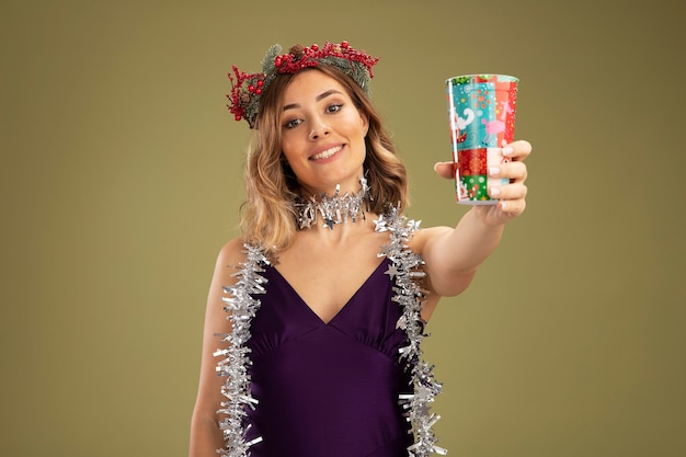 Linda garota sorridente com vestido roxo e grinalda com guirlanda no pescoço segurando um copo de natal para a câmera isolada em fundo verde oliva