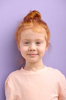 Linda garota sorridente criança caucasiana com cabelo ruivo e grandes olhos azuis isolados. garota ruiva natural com sardas olha para a frente com um rosto agradável, garota alegre e legal