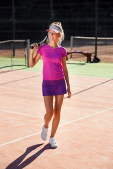 Linda garota sorridente de uniforme com raquete de tênis, andando na quadra de tênis ao ar livre.
