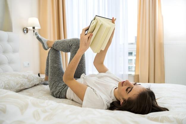 Linda garota sorridente, deitada na cama, escrevendo ou lendo seu livro pela manhã.