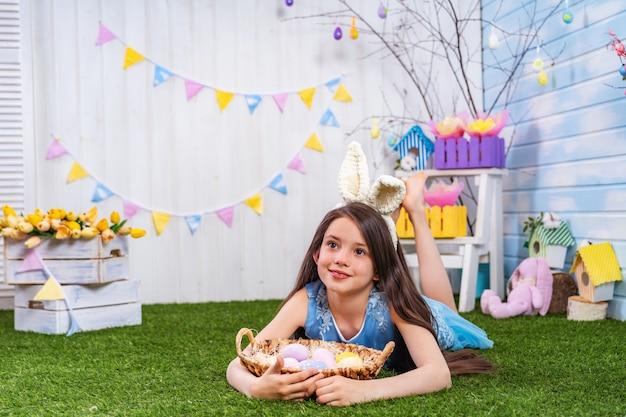 Linda garota sorridente, deitado na grama com ovos de páscoa e desviar o olhar.