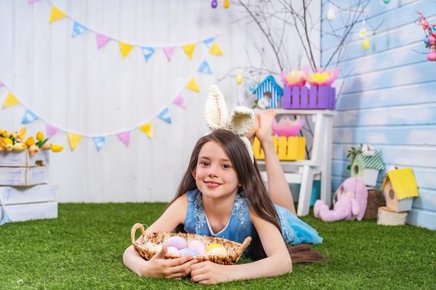 Linda garota sorridente, deitado na grama com ovos de páscoa e olhando para o quadro.