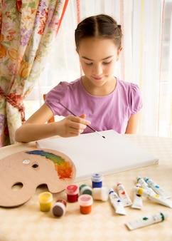 Linda garota sorridente desenhando com tintas a óleo sobre tela