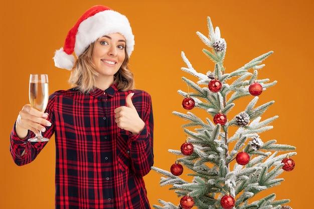 Linda garota sorridente em pé perto da árvore de natal com chapéu de natal segurando uma taça de champanhe para a câmera mostrando o polegar isolado em um fundo laranja